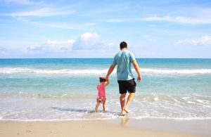 A father with a younger daughter on the beach.