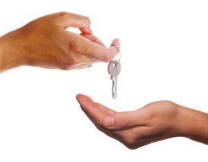 A landlord handing down keys to a tenant